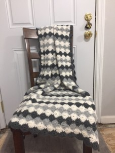 Crochet lap blanket in grey shades and shell stitches